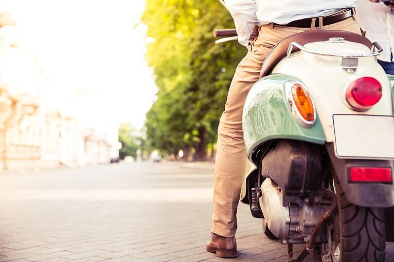 Closeup portrait of a scooter with male legs outdoors.jpeg