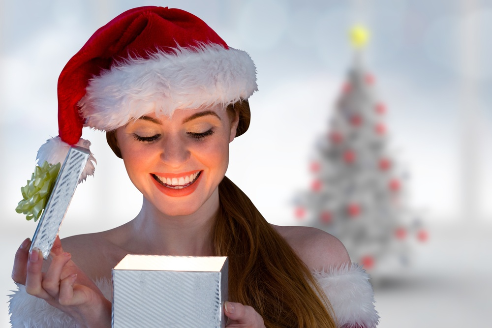 Sexy girl in santa costume opening a gift against blurry christmas tree in room